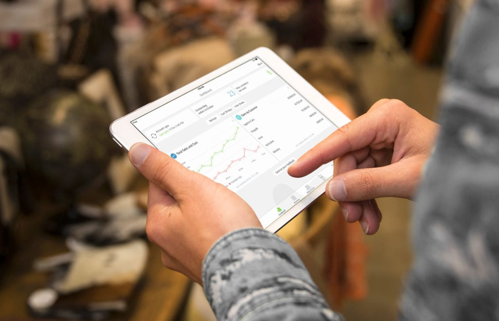 Person holds Apple iPad in hand with TradeGecko Analytics appearing on the screen